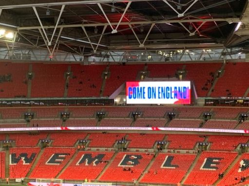 "A near-empty Wembley Stadium with ""Come on England"" on a big screen."