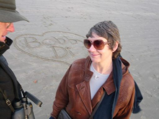 Bobby & Diddley on the beach. Drawn in the sand are the words 'Bobby' and 'Di' inside a heart.