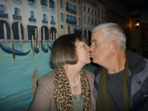 Bobby & Diddley sharing a kiss in front of a mural of Venice.