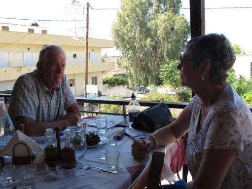Bobby and Diddley enjoying a meal in a restaurant overlooking a village in Crete.
