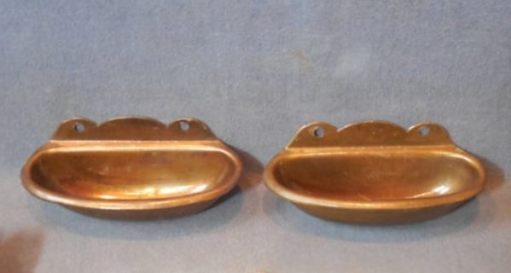 A pair of brass-effect cinema ashtrays.