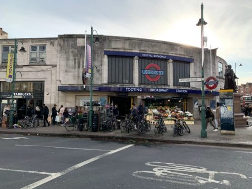 Exterior of Tooting Broadway Station. Slightly rundown looking, with a large number of bikes outside.