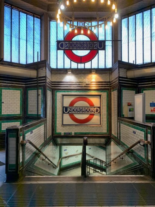 Stairway down in Tooting Bec Station, showing the rear of the roundel in the window, and another in tilework underneath.