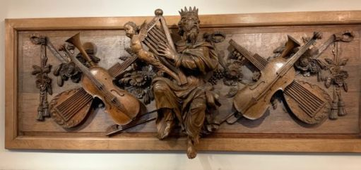 A beautiful carving depicting King David with a harp, surrounded by violins and lutes.