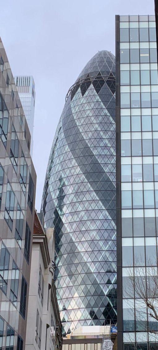 The Gherkin, almost hidden amongst even taller buildings.