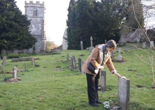 Diddley laying snowdrops on Frank's grave.