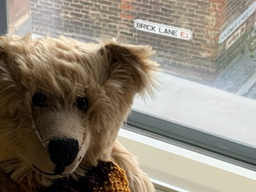 """Bertie in the window of Room 311 with the street name """"Brick Lane E1"""" visible outside."""