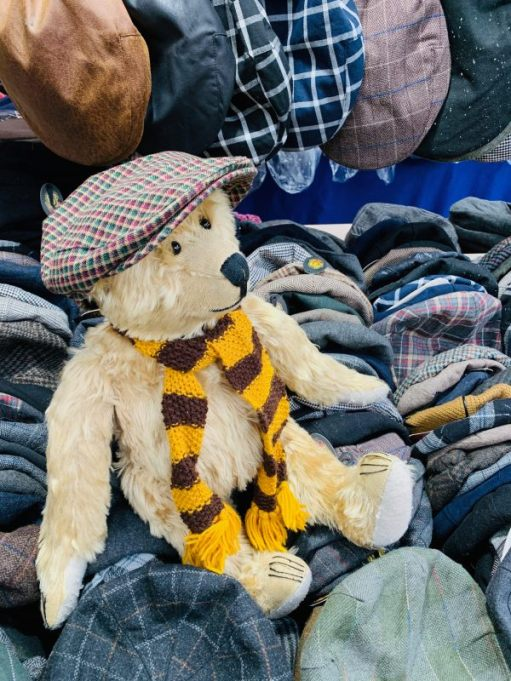 Close up of Bertie, wearing his Sutton United scarf and a flat cap, sat amongst the flat caps on the vintage hat stall in Spitalfields Market.