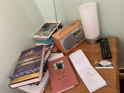 "A table loaded with books, a DAB radio, notebook a light and a ""Mindfully Bertie"" business card."