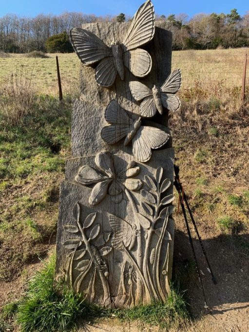 Wooden sculpture with butterflies carved into it.