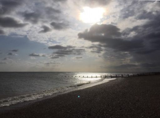 A picture of East Preston (EP) Beach, looking along the coast into the sun, which is reflecting off the water.