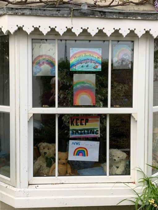 Bertie, Eamonn and Ellen in the window of Laurel Cottage with rainbows and NHS We Love You.