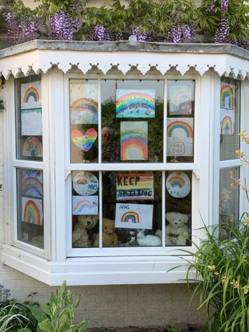 A bow window in Laurel Cottage with loads of messages and rainbows for the NHS.
