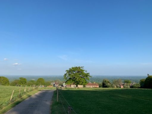 Looking down the North Downs. A very blue sky with ancient farm buildings and a few trees in the distance.