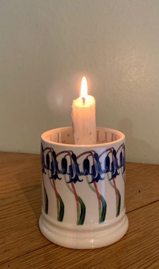 A candle lit for Diddley in a beautiful mug with painted Bluebells around the outside.