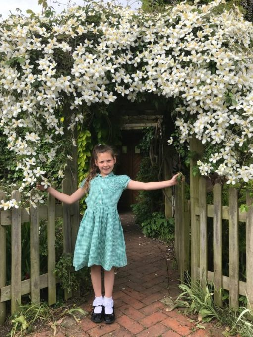 Kyla posing in front of the Clematis Montana wearing white ankle socks with black shoes and a summer dress.