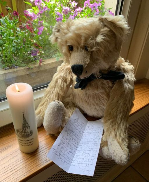 Lighting a Candle to Diddley: Bertie holding the letter sat on the windowsill with a lit candle.