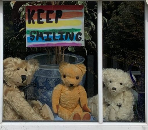 "Bertie, Eamonn and Trevor posing in the window of Laurel Cottage for story two hundred. An NHS rainbow with the words ""Keep Smiling"" is above them."