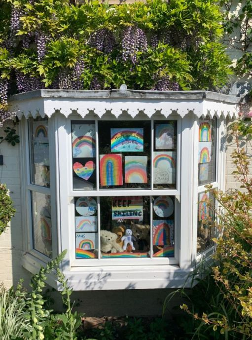 Trevor, Eamonn, Ellen, Bertie in the window of Laurel Cottage, with all the messages and rainbows supporting the NHS.