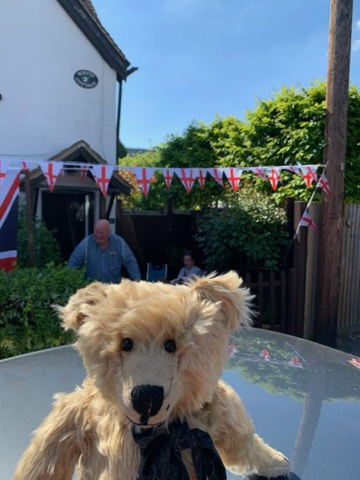 Bertie sat on a car roof with Bunting of English Flags decorating the garden behind.