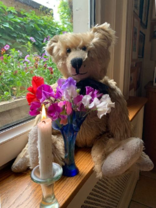 Bertie sat on the window sill at Laurel Cottage with a vase of colourful flowers and a candle lit for Diddly in front of him.