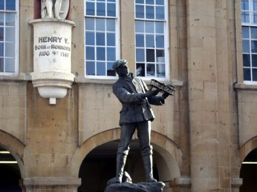 Bronze statue of Charles Rolls in Monmouth. He is holding a model aeroplane.