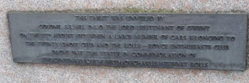 "Plaque under the statue: ""This tablet was unveiled by Colonel ER Hill DSO The Lord Lieutenent of Gwent on the 27th August 1977 when a large number cars belonging to the Twenty Ghost Club and the Rolls-Royce Enthusiast Club drove past this statue in commemeration of the centenary of the birth of Charles Stewart Rolls."