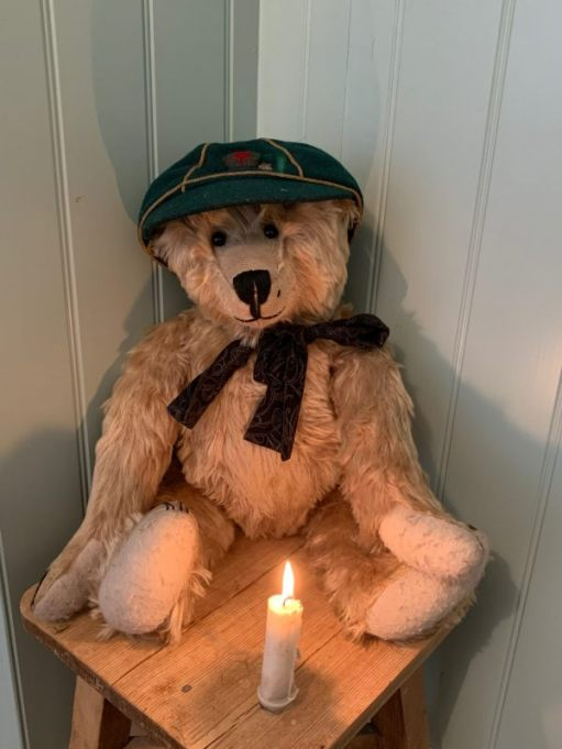 Bertie with Bobby's Wolf Cub cap sat behind a candle lit for Diddley..