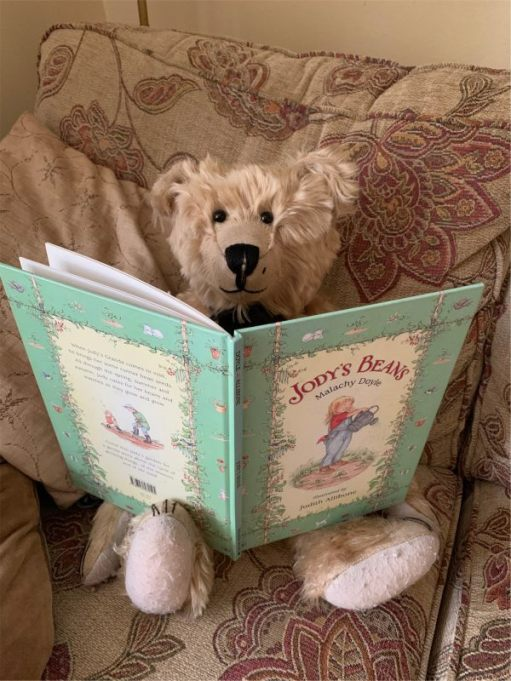 Bertie sat in an armchair reading the book Jody's Beans.
