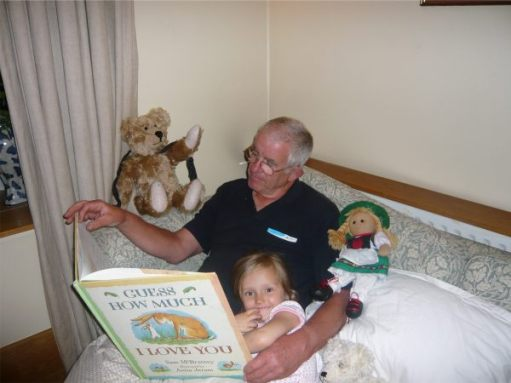 "Bobby reading the book ""Guess How Much I Love You"" to Layla, with Bertie and Heidi - an Austrian doll."