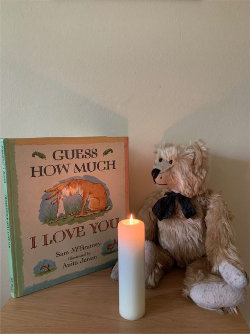 "Bertie looking at the book ""Guess How Much I Love You"", witha candle lit for Diddley in front."