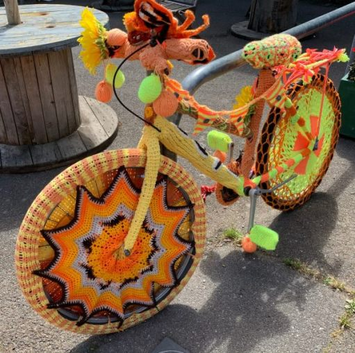 Yarnbomb Sisters - knitted bicycle, mainly yellows and browns.