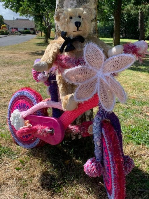 Yarnbomb Sisters - Bertie sat on a mainly pink knitted child's bicycle.