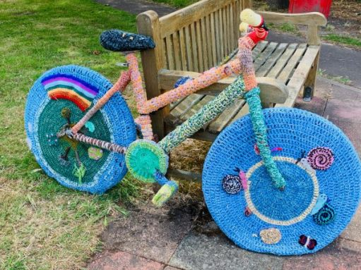 "Yarnbomb Sisters - bright blue knitted bicycle with ""NHS rainbow"" on rear wheel."