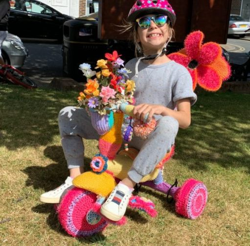 Yarnbomb Sisters - knitted child's tricycle (with child!)