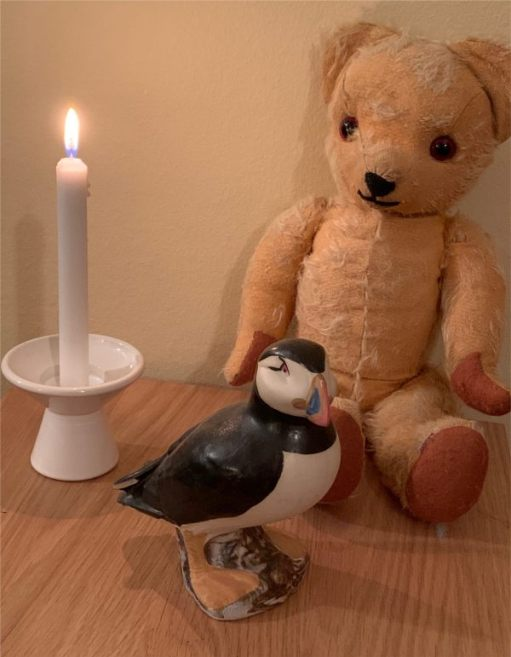 Eamonn, a china Puffin ornament and a candle lit for Diddley.
