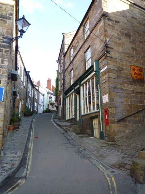 Narrow roadway between stone buildings heading down towards Robin Hood's Bay.
