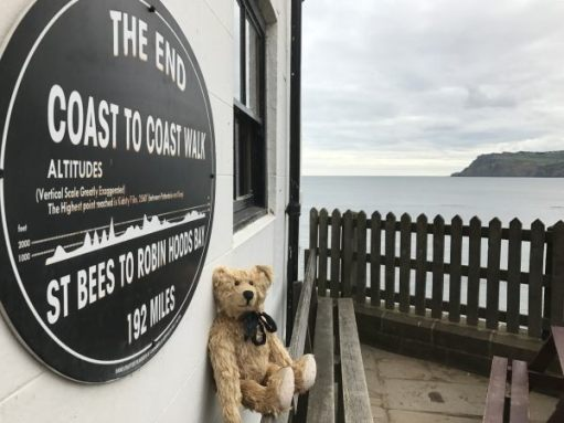 Bertie sat on a bench on front of a plaque marking the end of the Coast to Coast Walk - all 192 miles of it! A view of the bay in the background.