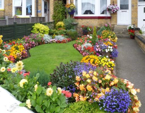 Beautifully manicured lawn and immaculate, brightly coloured flower beds.