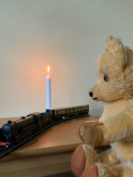 Eamonn waving at a model train with a Pullman Carriage and a candle lit for Diddley.