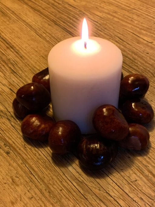 A Candle lit for Diddley, surrounded by conkers.