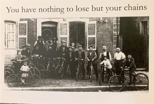 "Old Black & White newspaper photograph of several men on their pedal bikes outside a row a terraced houses facing straight onto the pavement. Caption above reads ""You have nothing to lose but your chains."""