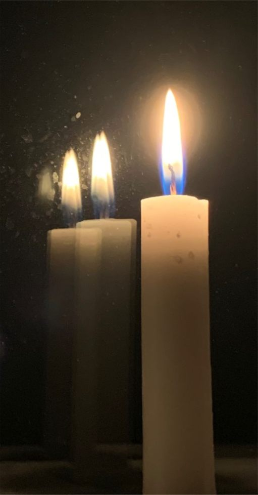 A candle lit for Diddley, reflected in a mirror.