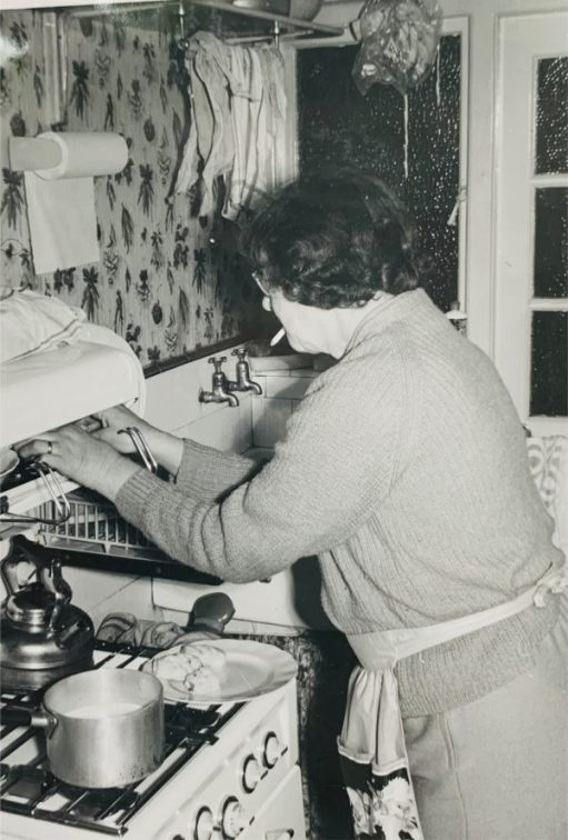 Time to Remember: Black & White picture of Bobby's Mum, Dolly, in the kitchen with her hands in the eye-level grill, cigarette in mouth.