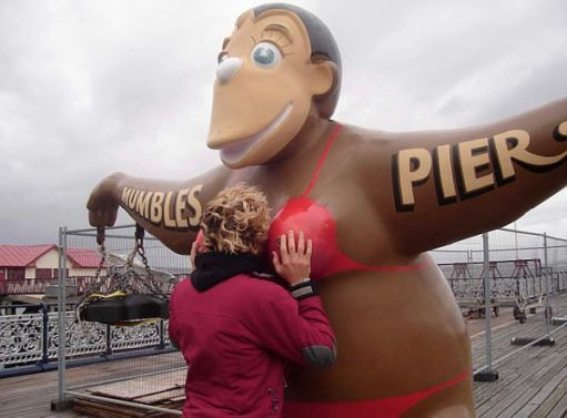 "A bikini-clad monkey with ""Mumbles Pier"" across its arms. A lady has her face buried in its cleavage!"