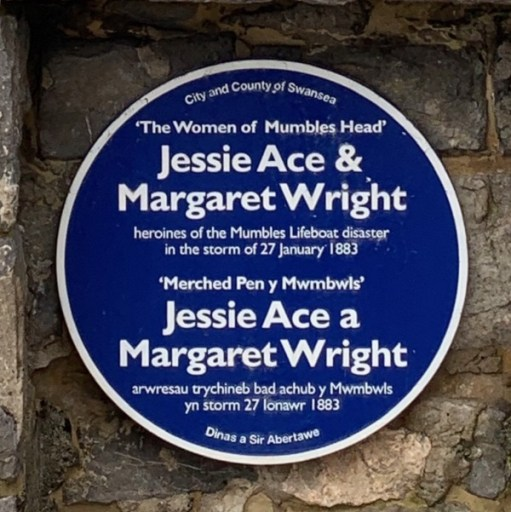 "Close up of the memorial plaque. ""City and County of Swansea 'The Women of Mumbles Head' Jessie Ace & Margaret Wright heroines of the Mumbles Lifeboat disaster in the storm of 27 January 1883"". Written in English and Welsh."