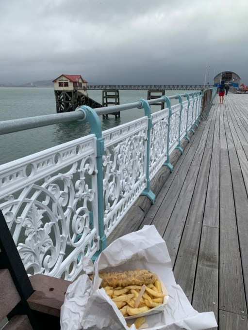 Looking down Mumbles Pier, with Bobby's Sausage & Chips in paper on a bench in the foreground.