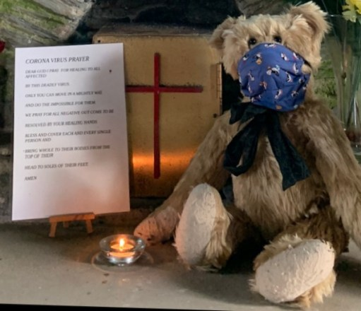 """Bertie, wearing his face mask, in a church with a candle lit for Diddley. Alongside is a Corona Virus prayer: """"Dear God, I pray for healing to all affected by this deadly virus. Only You can move in a mighty way and do the impossible for them. We pray for all negative outcome to be resolved by Your healing hands. Bless and cover each and every single person and bring whole to their bodies from the top of their head to the soles of their feet. Amen."""""""