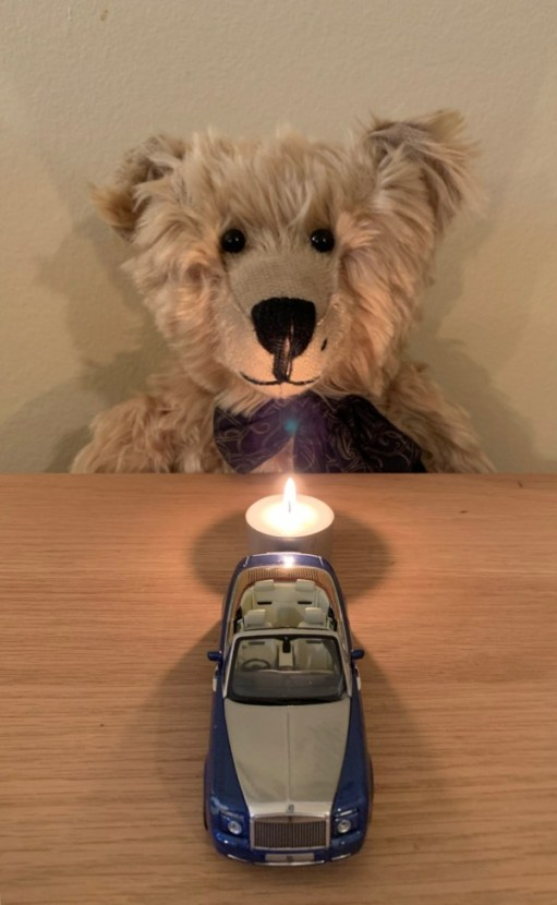 Bertie sat at a table facing a candle lit for Diddley, with a model of a Rolls-Royce in front.