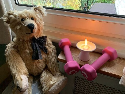 Bertie by the window with a candle lit for Diddley and two pink dumbells either side.